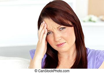 Cute woman with a headache sitting on a sofa at home