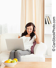 Cute woman with a notebook listening to music