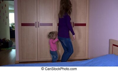 Cute woman with daughter girl take clothes from closet and measure it