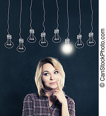 Cute Woman with Light Bulb on the Blackboard Background. Female with Idea Bulb