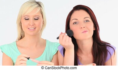 Cute women applying make-up in a studio