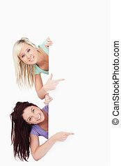 Cute Women peeking around a banner showing copyspace in a studio