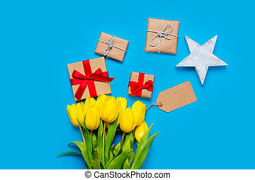cute yellow tulips, beautiful gifts and star shaped toy on the wonderful blue background