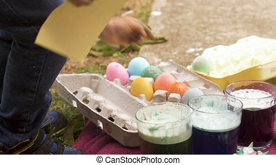 Cute young 3 year old girl grabbing a colored easter egg...