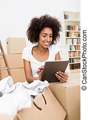 Cute young African American woman using a tablet