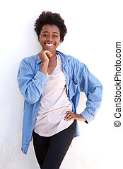 Cute young afro american woman with hand on chin and standing against white wall