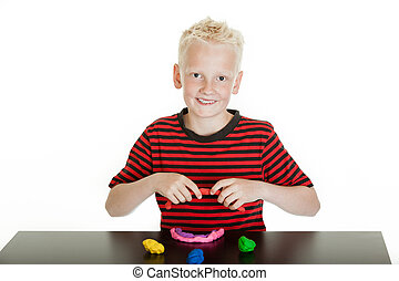 Cute young blond boy modeling with putty