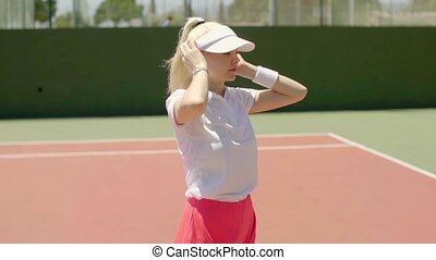 Cute young blond woman tennis player