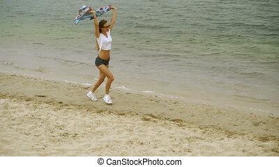 cute young blonde runs on a seashore