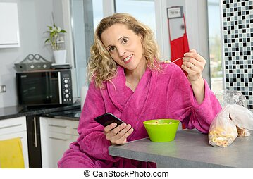 young blonde woman eating cereals and phone in the morning