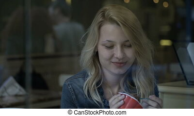 Cute young blonde woman eating ice cream in the pub waiting and smiling at people passing on the street