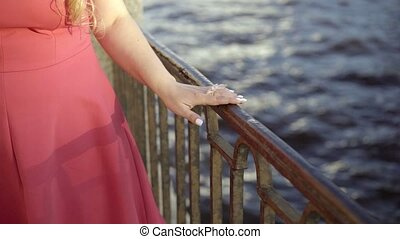 Cute young blonde woman in red dress walking on embankment