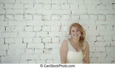 Cute young blonde woman in wedding dress posing in studio