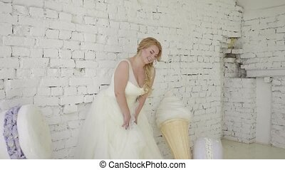 Cute young blonde woman in wedding dress posing for photographer in studio steadicam