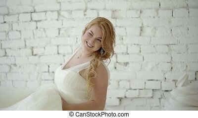 Cute young blonde woman in wedding dress posing and dancing in studio on background