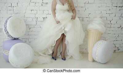 Cute young blonde woman in wedding dress posing and dancing in studio on background huge ice cream and macaroni