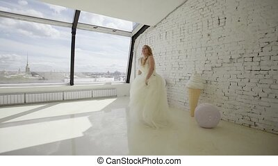 Cute young blonde woman in wedding dress posing for photographer in studio and circling