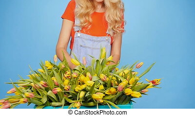 Young blonde woman with tulips on blue background - Cute...