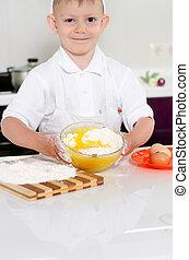 Cute young boy baking a cake
