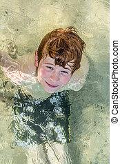 boy has fun in the ocean - cute young boy has fun in the...