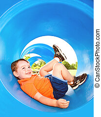 Cute young boy or kid playing in tunnel on playground.