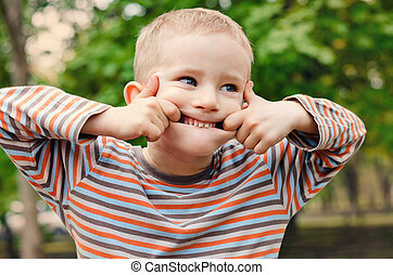 Cute young boy pulling a funny expression