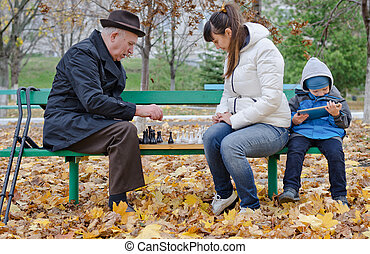 Cute young boy sitting on a park bench holding a tablet computer while his mother and grandfather play chess