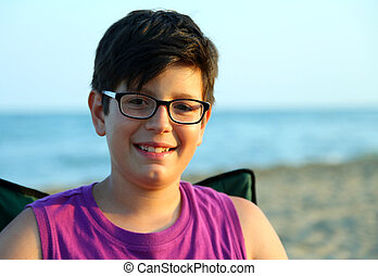 boy with glasses smiling on the sea shore