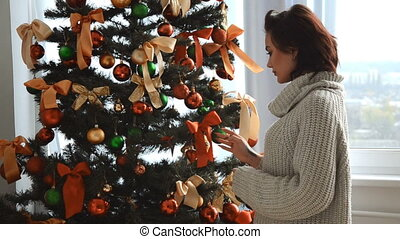 cute young brunette hangs on the tree toys morning