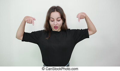 Cute young brunette woman in black t-shirt, blue jeans with belt on gray background, scared girl shows her index fingers down