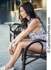 Cute young brunette woman sitting on the bench in summer street