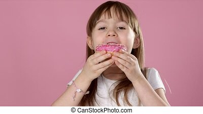 Cute young caucasian girl caught eating a sweet pink ...