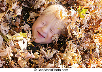Cute Young Child Laying in Pile of Fall Leaves