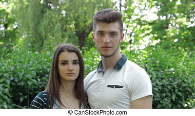 cute young couple at the park smiling on camera