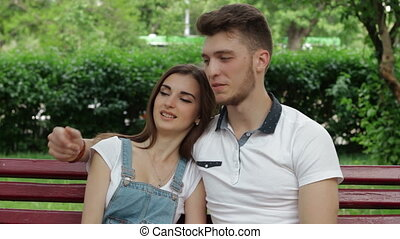 cute young couple cuddling and talking on a bench in the Park