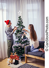 Cute, young couple decorating a Christmas tree