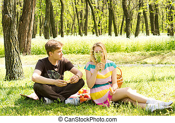 Cute young couple having food on picnic