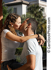 cute young couple kissing outside in tropical setting