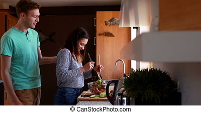 Cute young couple making a salad
