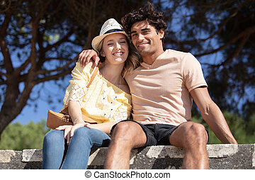 cute young couple sitting at park on the bench