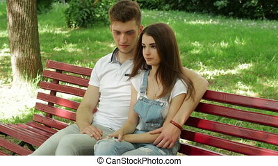 cute young couple talking in the Park on a bench