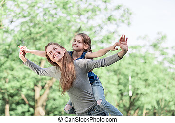 Cute young daughter on a piggy back ride with her mother