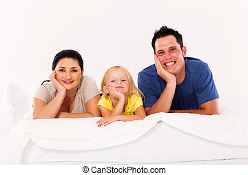 cute young family lying on bed at home