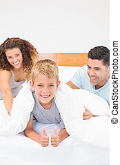 Cute young family messing about on bed at home in bedroom