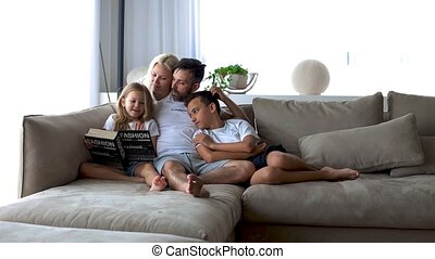 Cute young family spending time together at home. Little girl with blond hair reading a book with her parents and brother smiling happily. happy family