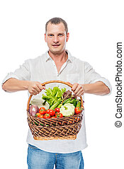 Cute young farmer with a harvest of vegetables on a white background