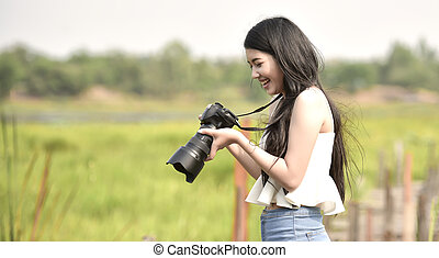 Cute young female photographer with camera outdoors at the park