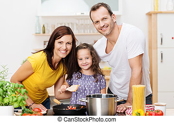 Cute young girl cooking with her parents
