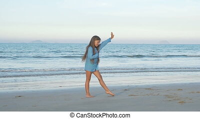 Cute young girl doing gymnastic cartwheel on the beach. Kid...