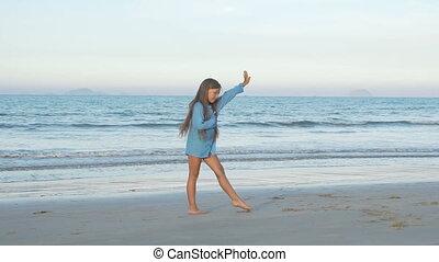 Cute young girl doing gymnastic cartwheel on the beach. Kid...